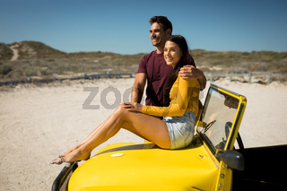 Happy caucasian couple, man embracing woman sitting on beach buggy by the sea