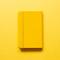 Yellow diary notebook isolated on yellow background. top view