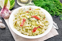 Fettuccine with zucchini and hot peppers in plate on napkin
