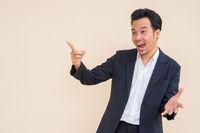 Portrait of surprised Asian businessman wearing suit against plain background