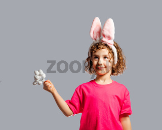 the cute little girl makes a wish for Easter