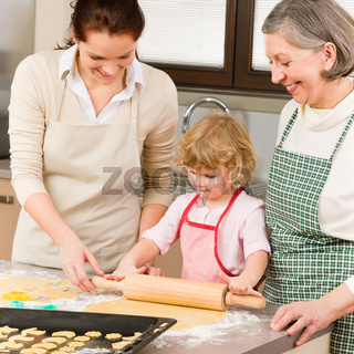 3 generations women rolling dough for baking