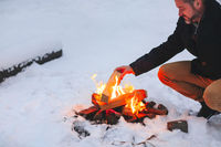 Mature man warming his hands with campfire in snowy forest