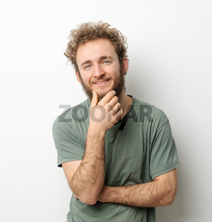 Curly hair smiling handsome young man looking at camera touching chin dressed in olive t-shirt isolated on white background. Portrait of smiling young man with hands folded
