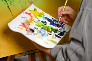 Female Artist mixes paints on the palette, painter at the studio, creator makes piece of art.