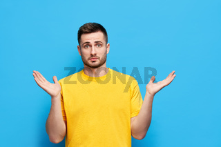 Young confused man spreads hands sideways feels doubt while makes choice