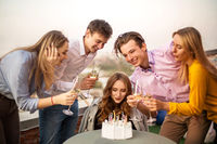 Young blond happy girl blows candles