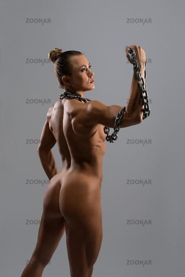 Strong naked woman with chain in studio