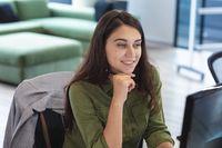 Caucasian female creative worker sitting at desk using computer