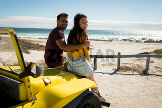 Happy caucasian couple sitting in beach buggy looking to camera