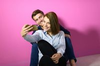 a happy young couple sitting on the floor in the house and making selfie