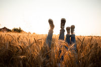 Couple's legs over grain field and sky