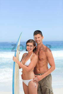 Lovers with their surfboard