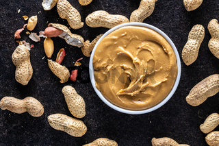 Peanut butter in bowl and peanuts