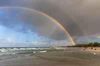 Himmel mit Regenwolken und doppeltem Regenbogen über der Ostseeküste bei Sehlendorf