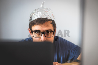 Conspiracy theory concept: young man is wearing aluminum head