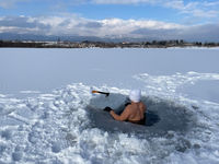 hardy man in ice water with snow with white cap