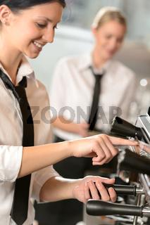 Smiling women waitress preparing coffee machine