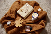 cup of marshmallow, book and glasses on sweater