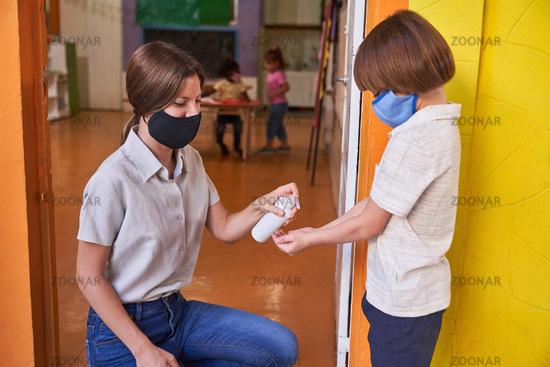 Erzieherin mit Mundschutz beim Hände desinfizieren