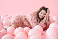 Fashion portrait of smiling pretty woman lying in many pink balloons