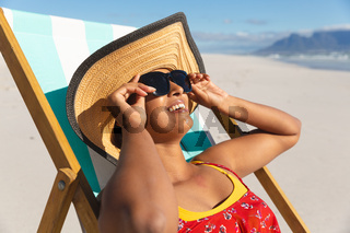 Smiling mixed race woman on beach holiday sitting in deckchair wearing sunglass sunbathing