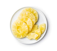 Canned sliced pineapple fruit on plate isolated on white background.