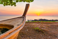 Wooden boat on sunset beach