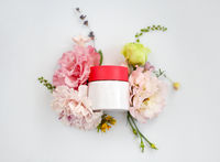 Flat lay of face cream with fresh rose flowers