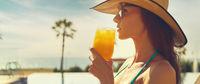 Woman wear straw hat drinks orange juice relaxing near pool