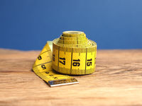 Yellow tailor tape measure on a wooden table, close up