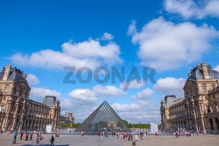 Louvre Courtyard With Tourists and Light Clouds in the Blue Sky
