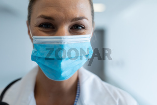 Portrait of happy caucasian female doctor wearing mask standing in hospital corridor