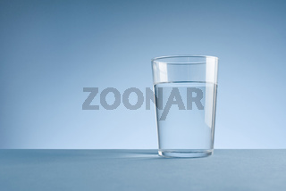 Minimalist photo of a glass of clean drinking water on blue background