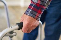 Hand von Senior Patient umfasst den Griff von Rollator