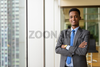 Portrait of handsome African businessman wearing suit and tie with arms crossed
