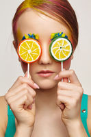 Teenager girl with unusual face art make-up . Child with lollipops in hands closing eyes.