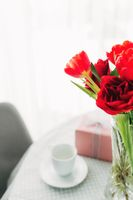 Bouquet of red tulips on table and white coffee cup. Concept for greeting card