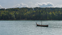 Replica of viking dragon boat for movie in mountain lake Walchensee in Bavaria, Germany on sunny day