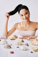 Smiling pretty afro woman with different seashells on white background