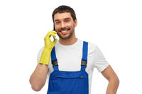 happy male worker or cleaner calling on smartphone