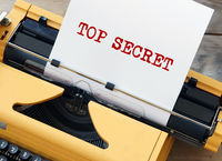 Top Secret on a white sheet of paper in old yellow typewriter