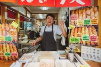 Friendly greeting vendor in his food stand selling fried japanese snack sticks with vegatables and fish in Miyajima, Hiroshima, Japan