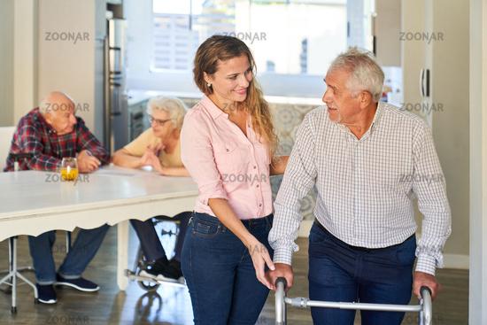 Pflegekraft hilft Senior beim laufen lernen mit Rollator