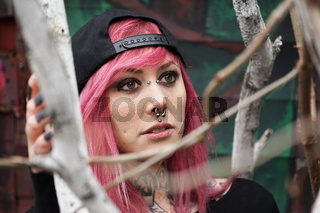 young woman with pierced face and tattooed neck behind tree branches
