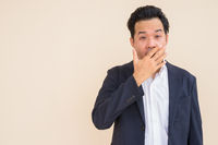 Portrait of Asian businessman wearing suit against plain background while looking shocked