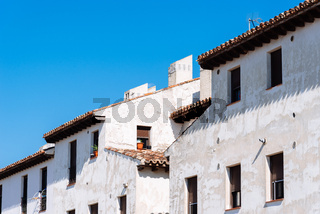 Old weathered white facades agaisnt blue sky
