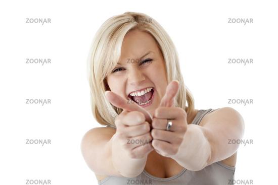 Blonde Frau hält ausgelassen lachend beide Daumen nach oben
