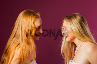 Two women standing opposite each other, touching by heads