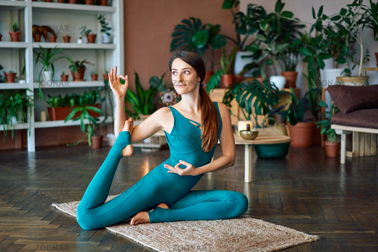 Young woman doing yoga asana Eka Pada Rajakapotasana one legged king pigeon at home